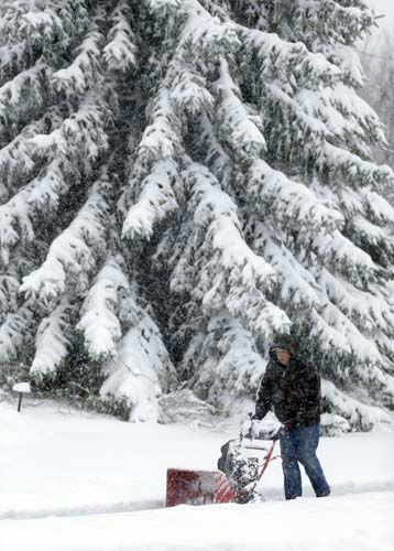 A homeowner clears the more than seven inches  of snow from his sidewalk in Carmel, Ind., Monday, March 25, 2013. &#40;AP Photo&#47;Michael Conroy&#41; <span class=meta>(AP Photo&#47; Michael Conroy)</span>