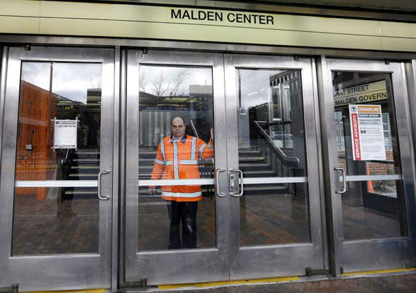 An MBTA transit official closes a door at Malden Center station in Malden, Mass. Friday, April 18, 2013 as area MBTA commuter trains are suspended. Two suspects in the Boston Marathon bombing killed an MIT police officer, injured a transit officer in a firefight and threw explosive devices at police during their getaway attempt in a long night of violence that left one of them dead and another still at large Friday, authorities said as the manhunt intensified for a young man described as a dangerous terrorist. &#40;AP Photo&#47;Elise Amendola&#41; <span class=meta>(AP Photo&#47; Elise Amendola)</span>