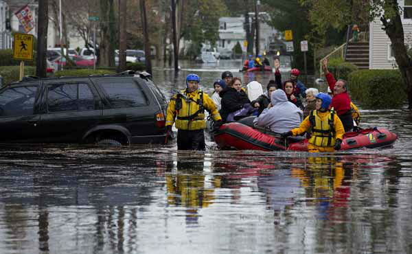 People, some waving to those on dry ground, are rescued by boat in Little Ferry, N.J. Tuesday, Oct. 30, 2012 in the wake of superstorm Sandy. Sandy, the storm that made landfall Monday, caused multiple fatalities, halted mass transit and cut power to more than 6 million homes and businesses. &#40;AP Photo&#47;Craig Ruttle&#41; <span class=meta>(AP Photo&#47; Craig Ruttle)</span>