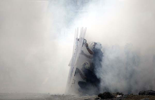 "<div class=""meta image-caption""><div class=""origin-logo origin-image ""><span></span></div><span class=""caption-text"">Riot policemen take cover behind their shields amid tear gas smoke during clashes in Taksim Square in Istanbul, Turkey, Tuesday, June 11, 2013. Hundreds of police in riot gear forced through barricades in Istanbul's central Taksim Square early Tuesday, pushing many of the protesters who had occupied the square for more than a week into a nearby park. (AP Photo/Kostas Tsironis) (AP Photo/ Kostas Tsironis)</span></div>"