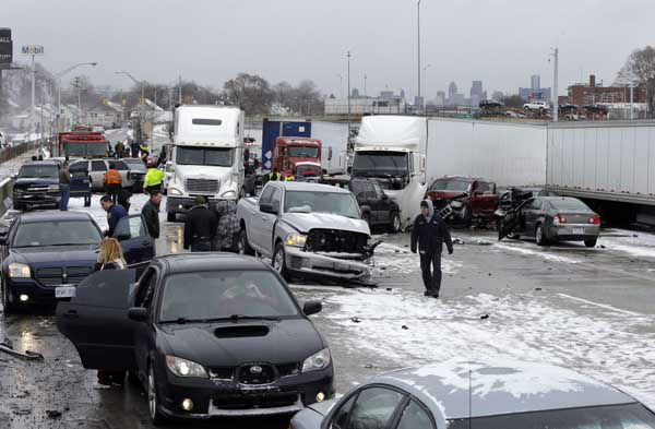 Snow squalls and slippery roads led to a series of accidents that left at least three people dead and 20 injured on a mile-long stretch of southbound I-75 in Detroit. More than two dozen vehicles, including tractor-trailers, were involved in the pileups. (AP Photo/Paul Sancya)
