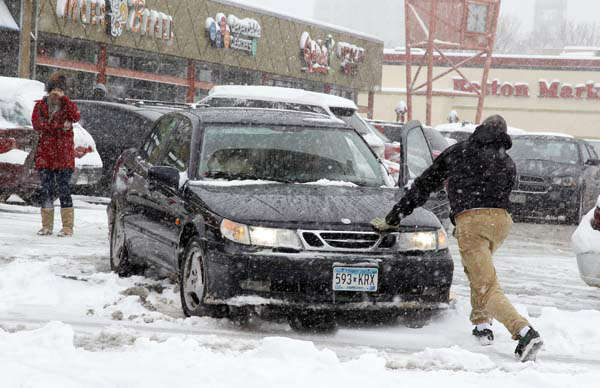 People work to free up a stuck car in a parking lot in central Denver as a spring storm packing high winds and heavy snow sweeps over Colorado&#39;s Front Range and on to the eastern plains on Saturday, March 23, 2013. Forecasters predict up to a foot of snow will fall in some locations in Colorado before the storm heads toward the nation&#39;s midsection. &#40;AP Photo&#47;David Zalubowski&#41; <span class=meta>(AP Photo&#47; David Zalubowski)</span>