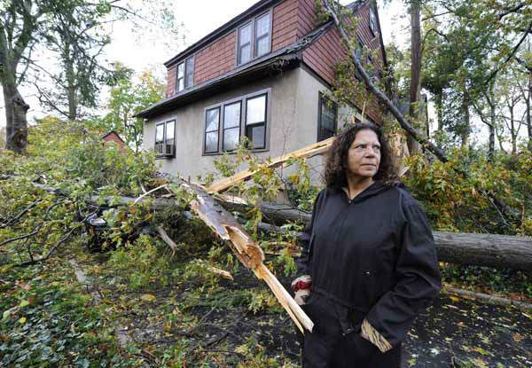 Arlene O&#39;Dell stands in front of her home where several trees fell, one crushing her car  on Barberry Lane, as a result of the powerful winds and rain of Hurricane Sandy on Tuesday, Oct., 30, 2012, in Sea Cliff, N.Y. &#40;AP Photo&#47;Kathy Kmonicek&#41; <span class=meta>(AP Photo&#47; Kathy Kmonicek)</span>