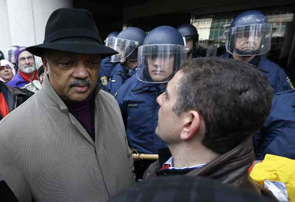 Rev. Jesse Jackson, left, and Lansing Mayor Virg Bernero, right, try to enter past Michigan State Police at the George W. Romney State Building, where Gov. Snyder has an office in Lansing, Mich., Tuesday, Dec. 11, 2012. The crowd is protesting right-to-work legislation passed last week. Michigan could become the 24th state with a right-to-work law next week. Rules required a five-day wait before the House and Senate vote on each other&#39;s bills; lawmakers are scheduled to reconvene Tuesday and Gov. Snyder has pledged to sign the bills into law. &#40;AP Photo&#47;Paul Sancya&#41; <span class=meta>(AP Photo&#47; Paul Sancya)</span>