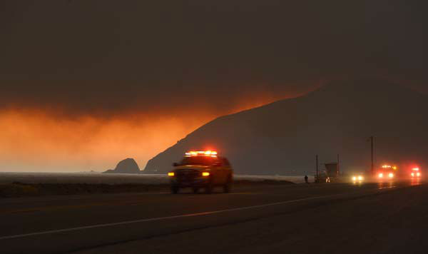 Fire department personnel drive along Pacific Coast Highway near Point Mugu as a thick layer of smoke sits overhead during a wildfire that burned several thousand acres, Thursday, May 2, 2013, in Ventura County, Calif.   &#40;AP Photo&#47;Mark J. Terrill&#41; <span class=meta>(AP Photo&#47; Mark J. Terrill)</span>