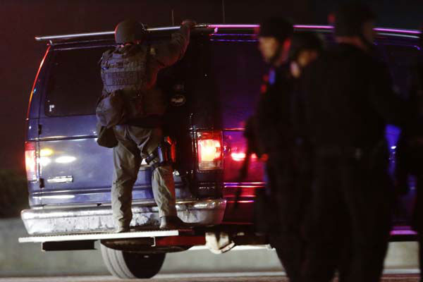 "<div class=""meta image-caption""><div class=""origin-logo origin-image ""><span></span></div><span class=""caption-text"">A police officers rides on the back of a van at a staging area as a manhunt is conducted for a suspect Friday, April 19, 2013, in Watertown, Mass. One of two suspects in the Boston Marathon bombing is dead and a massive manhunt is underway for another, authorities said early Friday April 19, 2013. Residents of Watertown, a Boston suburb, have been advised to keep their doors locked and not let anyone in.  (AP Photo/Matt Rourke) (AP Photo/ Matt Rourke)</span></div>"