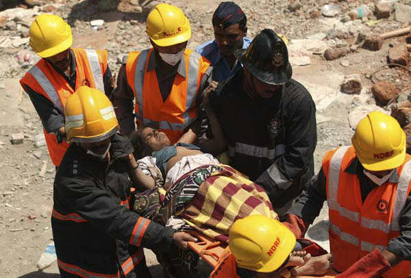 Indian rescue workers help an injured woman after a building collapse on the outskirts of Mumbai, India, Friday, April 5, 2013. The half-finished building that was being constructed illegally in a suburb of India&#39;s financial capital collapsed on Thursday, killing 35 people and injuring more than 50 others, police said Friday. &#40;AP Photo&#41; <span class=meta>(AP Photo&#47; RK MS SXJ TT**TOK**)</span>