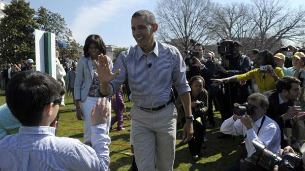 President Barack Obama, accompanied by first lady Michelle Obama, high-fives a participant in the annual Easter Egg Roll on the South Lawn of the White House in Washington, Monday, April 1, 2013. &#40;AP Photo&#47;Susan Walsh&#41; <span class=meta>(AP Photo&#47; Susan Walsh)</span>