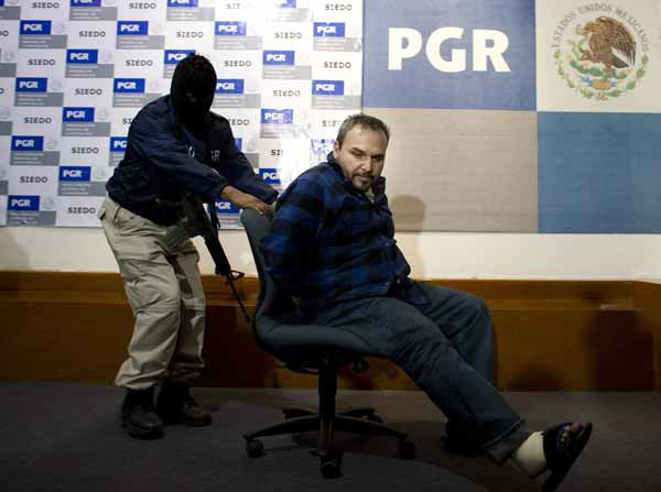 FILE - In this Oct. 22, 2008 file photo, a man identified by Mexico&#39;s Attorney General&#39;s office as Jesus Zambada Garcia, alias &#34;El Rey,&#34; or &#34;The King,&#34; an alleged leader in the Sinaloa drug cartel, is pushed in a chair by a masked police officer as Garcia is presented to the press in Mexico City. Experts say the killings and arrests of top cartel capos, like Zambada, have left lesser spawn to run the drug, kidnapping and extortion businesses; that has fueled a cruder approach and a psychopathic, mass-dismemberment style of killing, and is reflected in the new nicknames criminals are using to identify themselves. &#40;AP Photo&#47;Alexandre Meneghini, File&#41; <span class=meta>(AP Photo&#47; Alexandre Meneghini)</span>