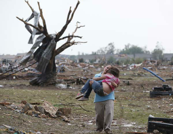 A woman carries her child through a field near the collapsed Plaza Towers Elementary School in Moore, Okla., Monday, May 20, 2013. &#40;AP Photo Sue Ogrocki&#41; <span class=meta>(AP Photo&#47; Sue Ogrocki)</span>