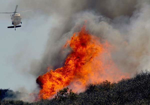 A helicopter makes a water drop on a hotspot over a hill near Thousand Oaks, Calif. on Thursday, May 2, 2013. Authorities have ordered evacuations of a neighborhood and a university about 50 miles west of Los Angeles where a wildfire is raging close to subdivisions. The blaze on the fringes of Camarillo and Thousand Oaks broke out Thursday morning and was quickly spread by gusty Santa Ana winds. Evacuation orders include California State University, Channel Islands. &#40;AP Photo&#47;Nick Ut&#41; <span class=meta>(AP Photo&#47; Nick Ut)</span>