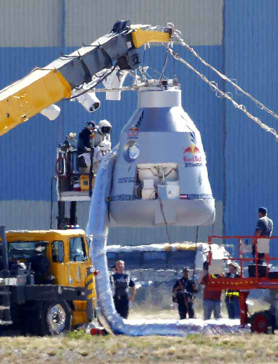Felix Baumgartner, in pressurized suit on platform at left, prepares to enter the balloon capsule in Roswell, N.M. on Tuesday, Oct. 9, 2012 in an attempt to break the speed of sound in a record-setting 23-mile-high jump. &#40;AP Photo&#47;Matt York&#41; <span class=meta>(AP Photo&#47; Matt York)</span>