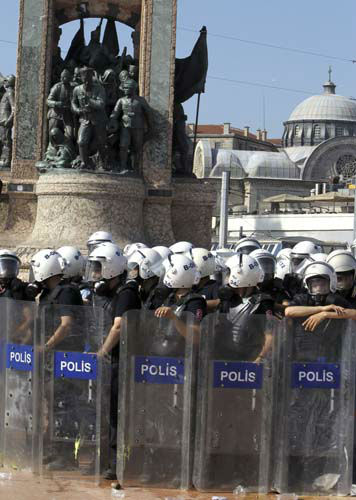 Police guard the monument of Mustafa Kemal Ataturk, founder of the modern Turkey,  during an operation at the Taksim Square in Istanbul, Turkey, on Tuesday, June 11, 2013. Hundreds of police in riot gear forced through barricades in the square early Tuesday, pushing many of the protesters who had occupied the square for more than a week into a nearby park. The Greek Orthodox church of Aghia Triada is seen in the background. &#40;AP Photo&#47;Thanassis Stavrakis&#41; <span class=meta>(AP Photo&#47; Thanassis Stavrakis)</span>