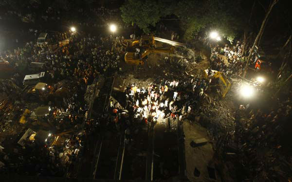 Rescue workers look for trapped people after a residential building collapsed in Thane, Mumbai, India, Thursday, April 4, 2013. At least 6 persons were killed and 40 were injured when an under-construction residential building collapsed on Thursday evening according to local reports.&#40;AP Photo&#47;Rafiq Maqbool&#41; <span class=meta>(AP Photo&#47; Rafiq Maqbool)</span>
