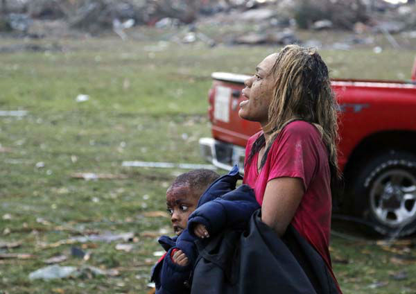 A woman carries an injured child to a triage center near the Plaza Towers Elementary School in Moore, Okla., Monday, May 20, 2013. A tornado as much as a mile &#40;1.6 kilometers&#41; wide with winds up to 200 mph &#40;320 kph&#41; roared through the Oklahoma City suburbs Monday, flattening entire neighborhoods, setting buildings on fire and landing a direct blow on an elementary school. &#40;AP Photo Sue Ogrocki&#41; <span class=meta>(AP Photo&#47; Sue Ogrocki)</span>
