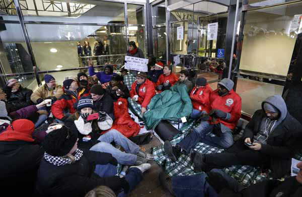 Protesters sit during a rally outside the doors of the George W. Romney State Building, where Gov. Snyder has an office in Lansing, Mich., Tuesday, Dec. 11, 2012. The crowd is protesting right-to-work legislation passed last week. Michigan could become the 24th state with a right-to-work law next week. Rules required a five-day wait before the House and Senate vote on each other&#39;s bills; lawmakers are scheduled to reconvene Tuesday and Gov. Snyder has pledged to sign the bills into law. &#40;AP Photo&#47;Paul Sancya&#41; <span class=meta>(AP Photo&#47; Paul Sancya)</span>