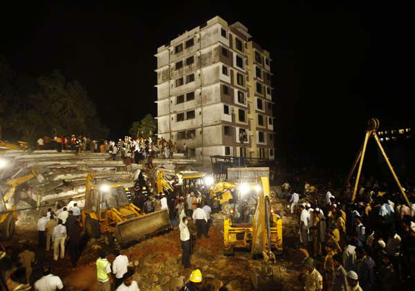Rescue workers search for trapped people after a building collapsed in Thane, Mumbai, India, Thursday, April 4, 2013. The building collapsed as it was being constructed illegally in a suburb, killing dozens of people, police said Friday. &#40;AP Photo&#47;Rafiq Maqbool&#41; <span class=meta>(AP Photo&#47; Rafiq Maqbool)</span>