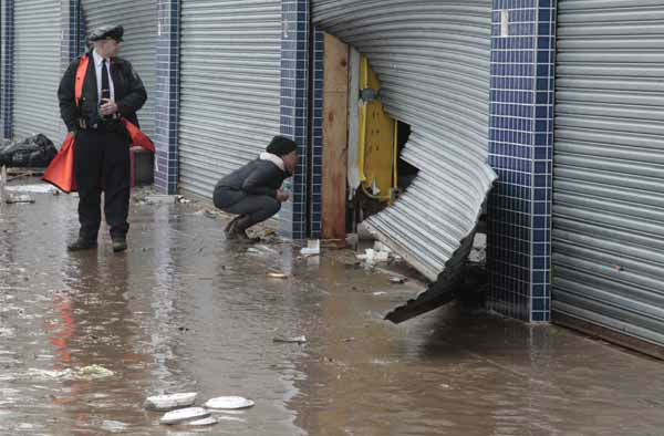 A police officer watch as a passerby look into a store through a damaged security grate, in the aftermath of Hurricane Sandy on Tuesday, Oct. 30, 2012, on Mermaid Avenue in Coney Island, N.Y.  Sandy, the storm that made landfall Monday, caused multiple fatalities, halted mass transit and cut power to more than 6 million homes and businesses.&#40;AP Photo&#47;Bebeto Matthews&#41; <span class=meta>(AP Photo&#47; Bebeto Matthews)</span>
