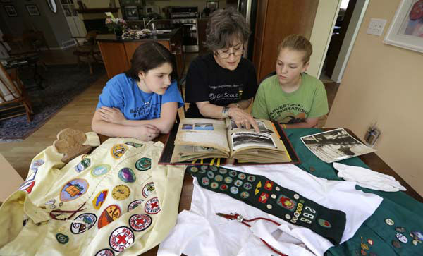 In this Tuesday, May 14, 2013 photo, Joni Kinsey, of Iowa City, Iowa, shows some of her Girl Scouts memorabilia to two girls in her troop in Iowa City, Iowa. In an effort to save money, Girl Scout councils across the country are making proposals that would have been unthinkable a generation ago: selling summer camps that date back to the 1950s. &#40;AP Photo&#47;Charlie Neibergall&#41; <span class=meta>(AP Photo&#47; Charlie Neibergall)</span>
