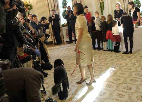First lady Michelle Obama, accompanied by first dog Bo, walks past reporters during a visit to the State Dining Room of the White House in Washington, Wednesday, Nov. 28, 2012, during a preview of the White House holiday decorations. The theme for the White House Christmas 2012 is Joy to All. School children were also in the State Dining Room decorating holiday treats. &#40;AP Photo&#47;Susan Walsh&#41; <span class=meta>(AP Photo&#47; Susan Walsh)</span>