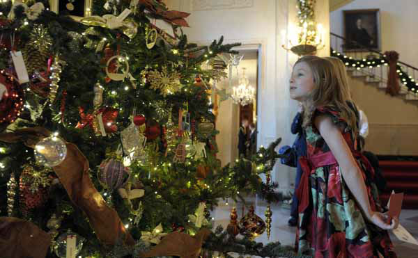 Olivia Marlow, 6, looks at a tree honoring presidential first ladies that is on display in the Grand Foyer of the White House in White House in Washington, Wednesday, Nov. 28, 2012, during a preview of the holiday decorations. The theme for the White House Christmas 2012 is Joy to All. &#40;AP Photo&#47;Susan Walsh&#41; <span class=meta>(AP Photo&#47; Susan Walsh)</span>