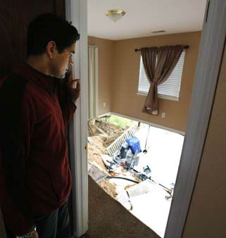 In this photo taken Monday, May 6, 2013, Jagtar Singh gazes from the doorway into one of the bedrooms that collapsed as the ground gave way beneath his home in Lakeport, Calif.  Shortly after Singh moved his wife, 4-year-old daughter and his parents the hill behind his home collapsed taking the underside of his home, leaving the carpet dangling.  Officials believe that water that has bubbled to the surface is playing a role, in the collapse of the hillside subdivision that has forced the evacuation of 10 homes and the notice of imminent evacuation of another 10 in this upscale subdivision.&#40;AP Photo&#47;Rich Pedroncelli&#41; <span class=meta>(AP Photo&#47; Rich Pedroncelli)</span>