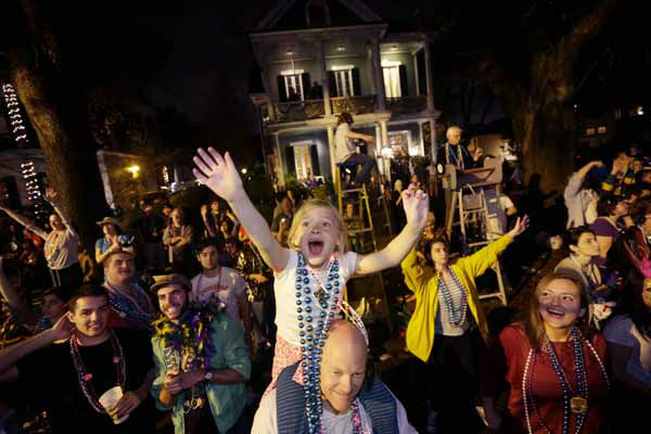 Addison Moran, 7, yells for beads and trinket from the shoulders of her father Paul Moran during the Krewe of Bacchus Mardi Gras parade in New Orleans, Sunday, Feb. 10, 2013. &#40;AP Photo&#47;Gerald Herbert&#41; <span class=meta>(AP Photo&#47; Gerald Herbert)</span>