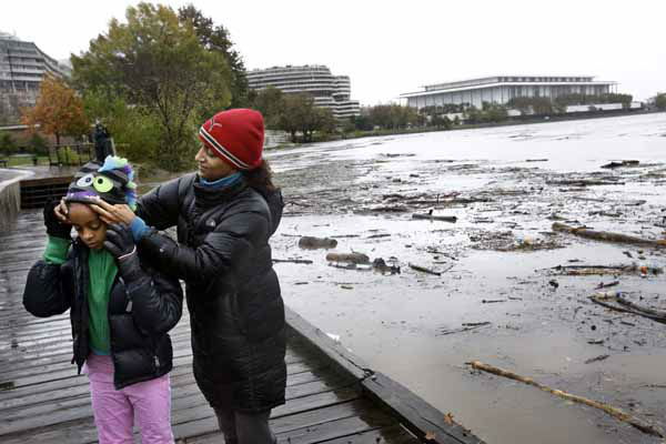 Sally Leakemariam of Washington, helps her daughter Nadia Zaki, 10, to put on a winter hat, as debris flows down the swollen Potomac River, with the Kennedy Center in the background, after Hurricane Sandy impacted the region, in the Georgetown waterfront neighborhood of Washington, on Tuesday, Oct. 30, 2012. &#40;AP Photo&#47;Jacquelyn Martin&#41; <span class=meta>(AP Photo&#47; Jacquelyn Martin)</span>