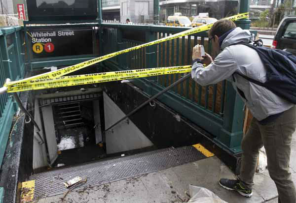 A man uses his mobile phone to photograph a closed and flooded subway station in lower Manhattan, in New York, Tuesday, Oct. 30, 2012. New York City awakened Tuesday to a flooded subway system, shuttered financial markets and hundreds of thousands of people without power a day after a wall of seawater and high winds slammed into the city, destroying buildings and flooding tunnels.  &#40;AP Photo&#47;Richard Drew&#41; <span class=meta>(AP Photo&#47; Richard Drew)</span>