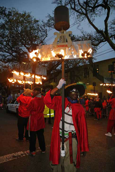 Flambeaux carries line up to march in the Orpheus Mardi Gras parade in New Orleans,  Monday, Feb. 11, 2013. The heavy torches were originally used to light the floats but now many krewes still keep the carries to keep the old-time tradition alive. &#40;AP Photo&#47;Bill Haber&#41; <span class=meta>(Photo&#47;Bill Haber)</span>