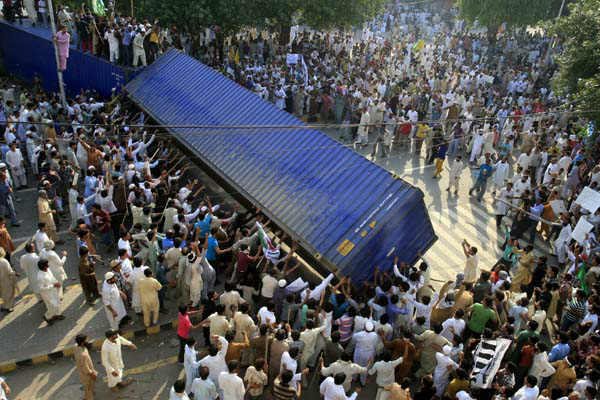 Pakistani protesters topple a shipping container police used to block the road to the US consulate in Lahore, Pakistan on  Friday, Sept 21, 2012. Tens of thousands protested around the country against an amateurish anti-Muslim film produced in the United States and vulgar caricatures of the Prophet Muhammad published in a French satirical weekly after the government encouraged peaceful protests and declared a national holiday ? &#34;Love for the Prophet Day.&#34; Demonstrations turned violent in several Pakistani cities and over a dozen people were killed and many more injured. &#40;AP Photo&#47;K.M. Chaudary&#41; <span class=meta>(AP Photo&#47; K.M. Chaudary)</span>