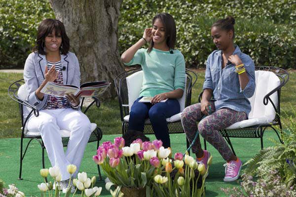 First lady Michelle Obama, with daughters Malia and Sasha, reads the book &#34;Cloudy With A Chance of Meatballs&#34; to children as part of the annual White House Easter Egg Roll, Monday, April 1, 2013, on the South Lawn of the White House in Washington. &#40;AP Photo&#47;Jacquelyn Martin&#41; <span class=meta>(AP Photo&#47; Jacquelyn Martin)</span>