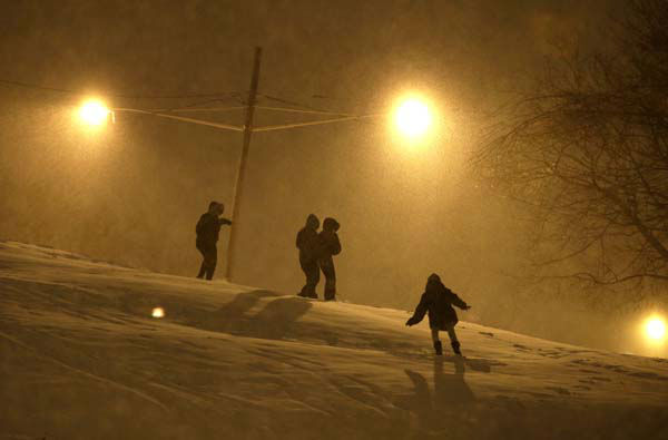 People walk on the snow covered hill of Leonard Gordon Park as snow falls over them, Thursday, Jan. 2, 2014, in Jersey City, N.J. Snow and bone-chilling temperatures are expected for the overnight hours with substantial accumulation predicted. &#40;AP Photo&#47;Julio Cortez&#41; <span class=meta>(Photo&#47;Julio Cortez)</span>
