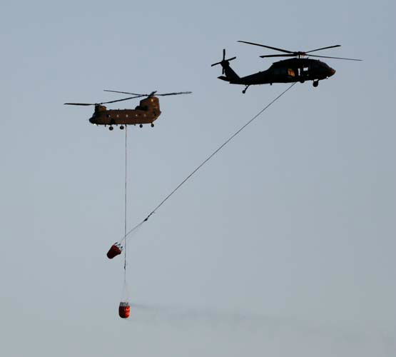 "<div class=""meta ""><span class=""caption-text "">Two U.S. Army helicopters pass each other as they help fight a wildfire in the Black Forest area north of Colorado Springs, Colo., on Tuesday, June 11, 2013. At least four major wildfires broke out along the front of the Rocky Mountains in Colorado Tuesday, burning a handful of houses and chasing people from thousands of homes in hot, gusty weather. (AP Photo/Ed Andrieski) (AP Photo/ Ed Andrieski)</span></div>"