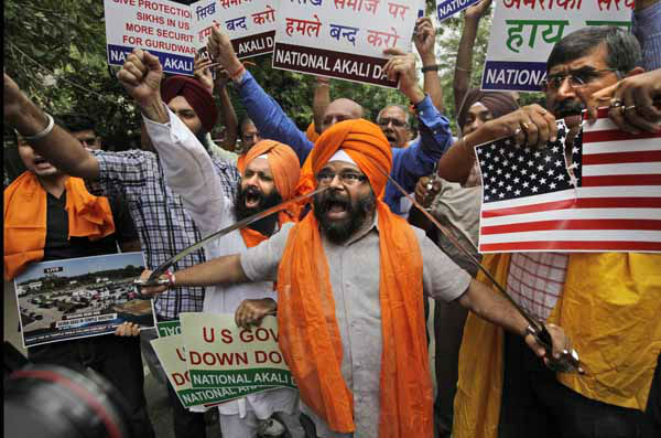 "<div class=""meta image-caption""><div class=""origin-logo origin-image ""><span></span></div><span class=""caption-text"">Indian Sikhs holding swords shout slogans during a protest in New Delhi, India , Monday, Aug. 6, 2012 against Sunday's killing of 6 people at the Sikh temple in the United States. Indian Prime Minister Manmohan Singh said Monday that he was shocked and saddened by the shooting attack that killed six people at a Sikh house of worship in the U.S. state of Wisconsin. (AP Photo/ Manish Swarup) (AP Photo/ Manish Swarup)</span></div>"