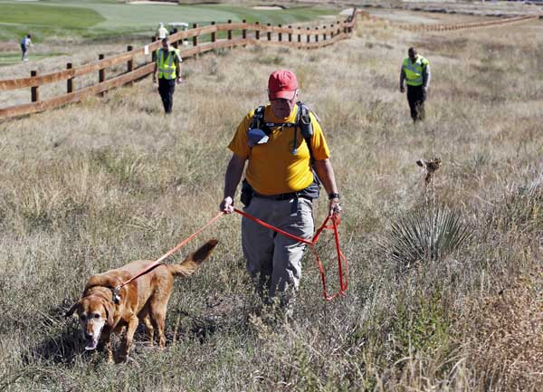 Denis McLaughlin leads his search and rescue dog through a field of tall grass searching for ten-year-old Jessica Ridgeway near her home in Westminster, Colo., on Monday, Oct. 8, 2012. The youngster has been missing since she left her home Friday morning on her way to school. <span class=meta>(AP Photo&#47;Ed Andrieski)</span>