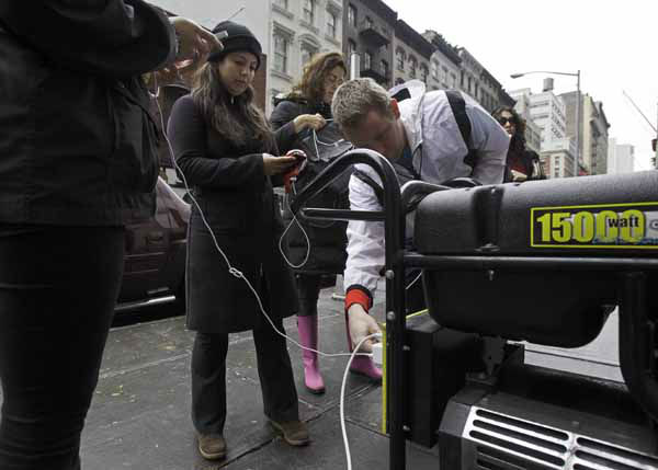 People in New York&#39;s Tribeca neighborhood, without power because of superstorm Sandy, wait for a chance to charge their mobile phones on an available generator setup on a sidewalk, Tuesday, Oct. 30, 2012.  Sandy, the storm that made landfall Monday, caused multiple fatalities, halted mass transit and cut power to more than 6 million homes and businesses. &#40;AP Photo&#47;Richard Drew&#41; <span class=meta>(AP Photo&#47; Richard Drew)</span>