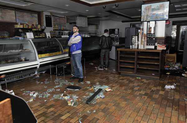 Workers in a deli near New York&#39;s Financial District survey Hurricane Sandy damge to their establishment, Tuesday, Oct. 30, 2012.  &#40;AP Photo&#47;Richard Drew&#41; <span class=meta>(AP Photo&#47; Richard Drew)</span>