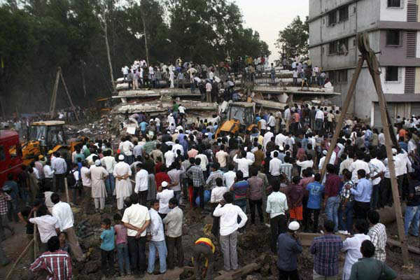 People gather as rescue workers look for trapped people after a building collapsed in Thane, Mumbai, India, Thursday, April 4, 2013. At least two persons were killed and sixteen injured, according to a Press Trust of India report. &#40;AP Photo&#41; <span class=meta>(AP Photo&#47; RSI DA**LON**)</span>