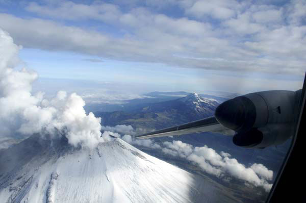 In this image released by the Mexican Navy &#40;SEMAR&#41;, steam and ash rise from the crater of the Popocatepetl volcano, left, on the outskirts of Mexico City as seen from inside a navy aircraft as it approaches the volcano on Wednesday, July 10, 2013. Behind at right is the volcano Iztaccihuatl.  Last Saturday, Mexico&#39;s National Center for Disaster Prevention raised the volcano alert from Stage 2 Yellow to Stage 3 Yellow, the final step before a Red alert, when possible evacuations could be ordered after the Popocatepetl volcano spit out a cloud of ash and vapor 2 miles &#40;3 kilometers&#41; high over several days of eruptions. &#40;AP Photo&#47;SEMAR&#41; <span class=meta>(AP Photo&#47; SEMAR)</span>