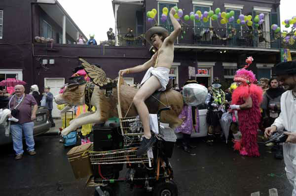 "<div class=""meta ""><span class=""caption-text "">A man dressed in a diaper rides a mechanical dog with wings in the French Quarter during Mardi Gras in New Orleans, Tuesday, Feb. 12, 2013.  Despite threatening skies, the Mardi Gras party carried on as thousands of costumed revelers cheered glitzy floats with make-believe monarchs in an all-out bash before Lent.   Crowds were a little smaller than recent years, perhaps influenced by the forecast of rain. Still, parades went off as scheduled even as a fog settled over the riverfront and downtown areas. (AP Photo/Gerald Herbert)</span></div>"