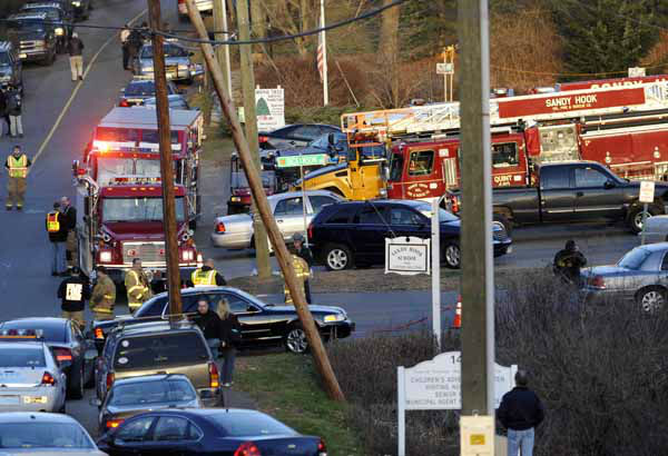 Emergency vehicles line the road at a firehouse staging area for family at the entrance to Sandy Hook School, the site of a school shooting in Newtown, Conn., Friday, Dec. 14, 2012. A man opened fire Friday inside two classrooms at the school where his mother worked as a teacher, killing 26 people, including 20 children.  The killer, armed with two handguns, committed suicide at the school and another person was found dead at a second scene, bringing the toll to 28, authorities said. A law enforcement official identified the gunman as 20-year-old Adam Lanza.  &#40;AP Photo&#47;Jessica Hill&#41; <span class=meta>(AP Photo&#47; Jessica Hill)</span>