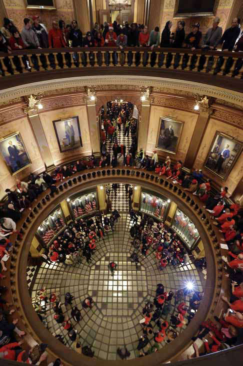 Protesters gather for a rally in the State Capitol rotunda in Lansing, Mich., Tuesday, Dec. 11, 2012. The crowd is protesting right-to-work legislation passed last week. Michigan could become the 24th state with a right-to-work law next week. Rules required a five-day wait before the House and Senate vote on each other&#39;s bills; lawmakers are scheduled to reconvene Tuesday and Gov. Snyder has pledged to sign the bills into law. &#40;AP Photo&#47;Paul Sancya&#41; <span class=meta>(AP Photo&#47; Paul Sancya)</span>