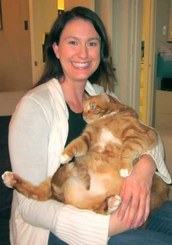 "<div class=""meta ""><span class=""caption-text "">In this photo provided by Brittney Barton, Barton, a veterinarian, poses for a photo with Skinny the cat Friday, March 8, 2013 in Dallas.The obese stray cat found wandering six months ago near Dallas has slimmed down from 41 to 34 pounds and has been adopted by the Barton, who has been overseeing his care.  (AP Photo/Todd Barton)</span></div>"