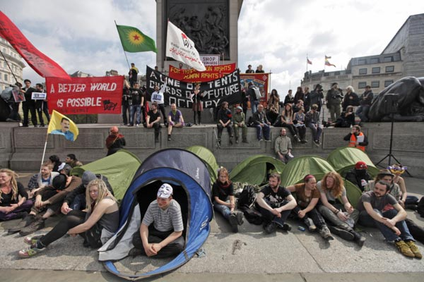 "<div class=""meta ""><span class=""caption-text "">Protesters from the 'Occupy London' movement, bottom, gather during a rally to mark May Day in central London, Tuesday, May 1,  2012. (AP Photo/Lefteris Pitarakis)</span></div>"