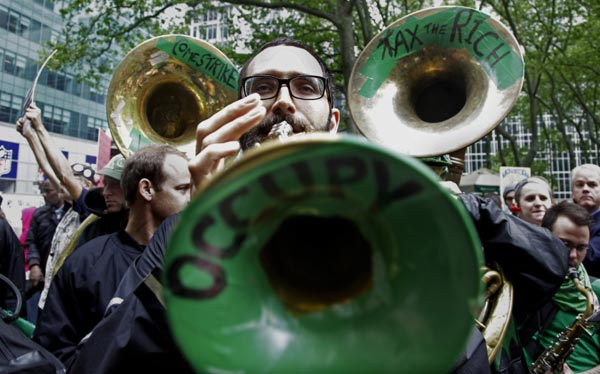 Trumpeter Andrew Morton, a member of the Rude Mechanical Orchestra from Brooklyn, N.Y.,  performs with the group as protesters gather at Bryant Park to prepare for a May Day march on Tuesday, May 1, 2012 in New York. (AP Photo/Bebeto Matthews)