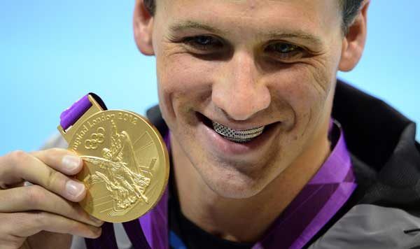 USA&#39;s Ryan Lochte holds up his gold medal after winning the men&#39;s 400 metre medley at the Aquatic Centre in the Olympic Village at the 2012 Summer Olympics in London on Saturday, July 28, 2012.  <span class=meta>(AP Photo&#47;Sean Kilpatrick, Canadian Press)</span>