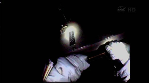 "<div class=""meta ""><span class=""caption-text "">Standing on the end of the station's main robotic arm, Hopkins clutched the 780-pound, refrigerator-size pump with both hands as he headed toward its installation spo (WLS Photo)</span></div>"