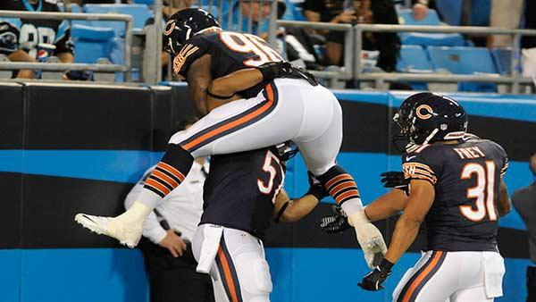 Chicago Bears' Kyle Moore (96) jumps onto teammate Jon Bostic (57) after Bostic's interception return for a touchdown during the first half of a preseason NFL football game in