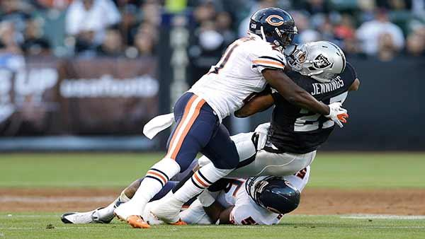 Chicago Bears strong safety Major Wright (21) and outside linebacker Lance Briggs (55) tackle Oakland Raiders running back Rashad Jennings (27) , Friday, Aug. 23, 2013. (AP Photo/Marcio Jose Sanchez